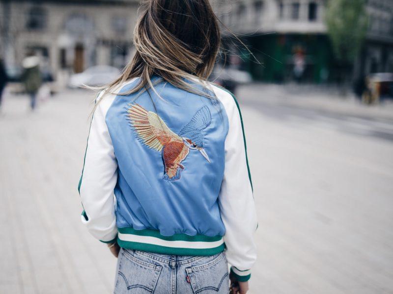 Look sport chic bomber brodé coloré, top lingerie, jean Levis, escarpins nude et sac Saint Laurent dos