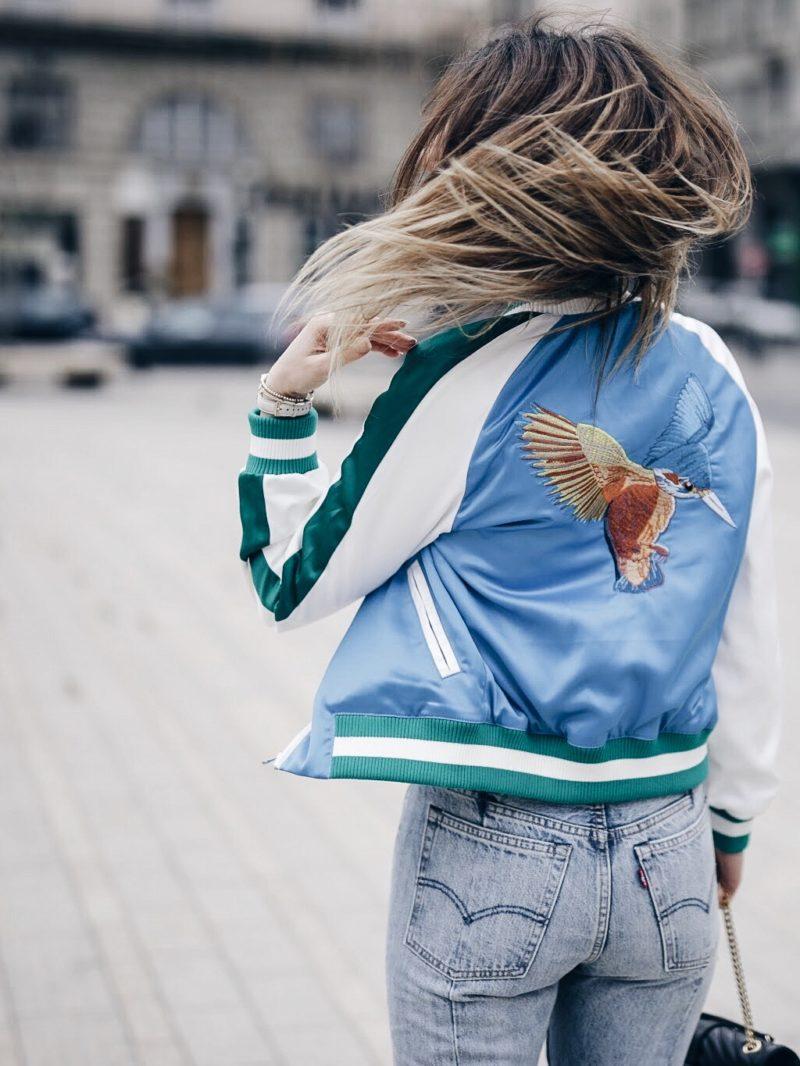 Look sport chic bomber brodé coloré, top lingerie, jean Levis, escarpins nude et sac Saint Laurent dos cheveux